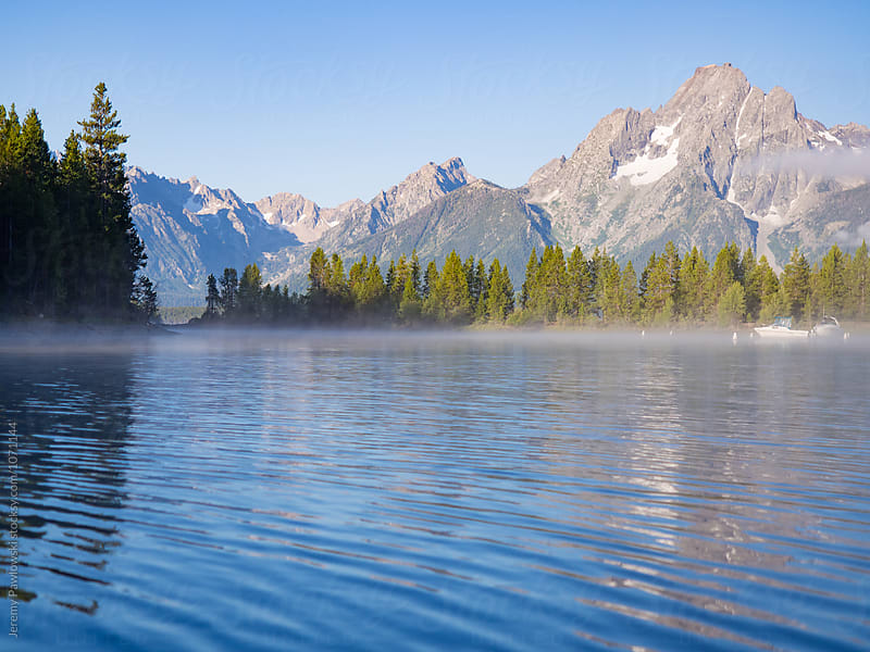 Landscape of early morning mist on water in front of mountain peaks and trees. Wyoming. by Jeremy Pawlowski for Stocksy United