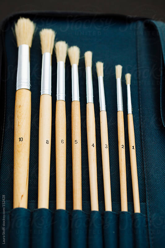 Different sized and numbered paint brushes in their case by Laura Stolfi for Stocksy United