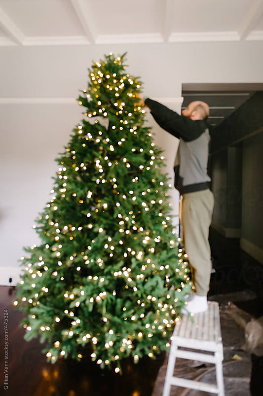 blurred image of man putting up christmas tree by Gillian Vann for Stocksy United