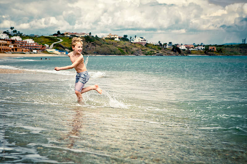Boy Playing Running in the Surf by Stephen Morris for Stocksy United
