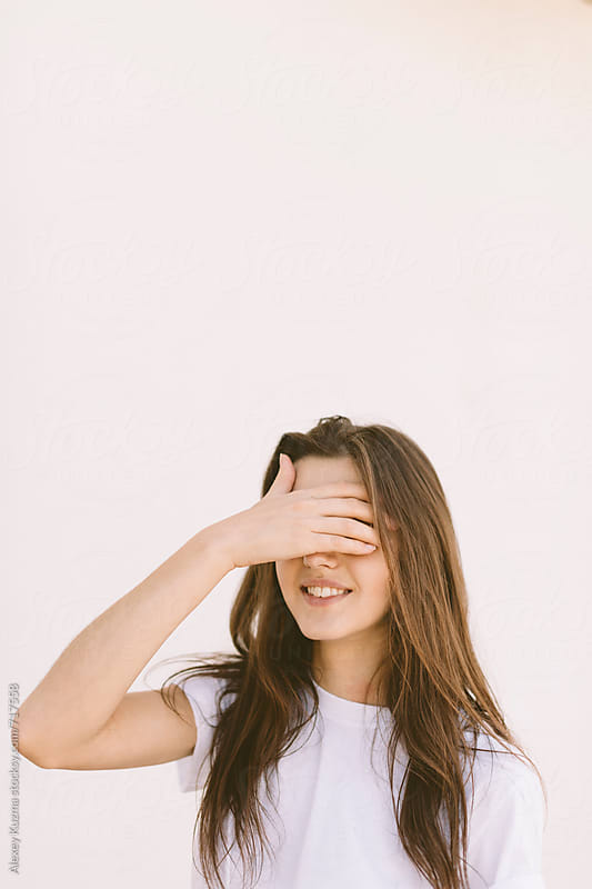 Young woman covering her face with hand by Vesna for Stocksy United