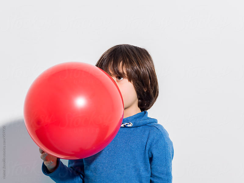 5 year old boy blowing a red balloon by Nasos Zovoilis for Stocksy United