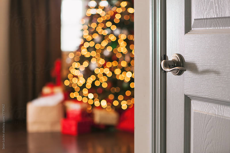 Christmas: Tree And Wrapped Gifts Wait Around The Corner by Sean Locke for Stocksy United