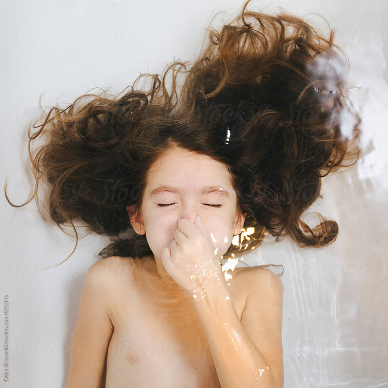 Child playing in bathtub. by Dejan Ristovski for Stocksy United