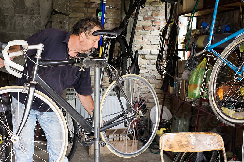 Man Repairing a Bike in a Garage by Mosuno for Stocksy United