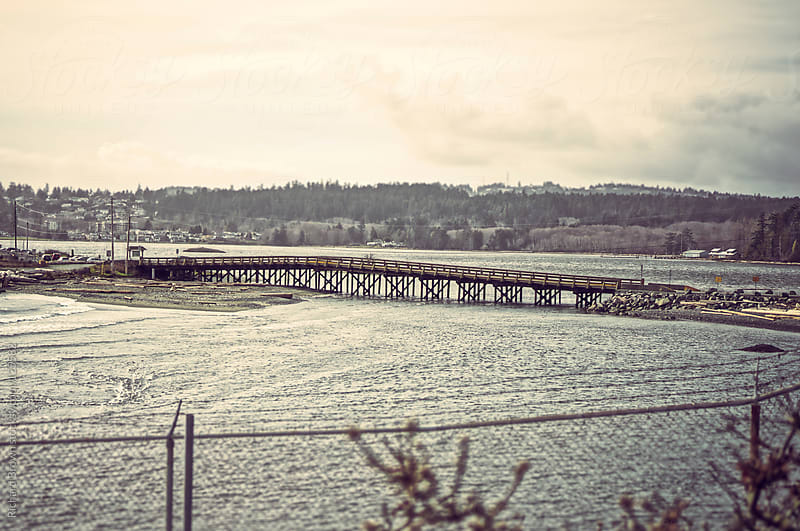 Bridge over the water on a cloudy day. by Richard Brown for Stocksy United