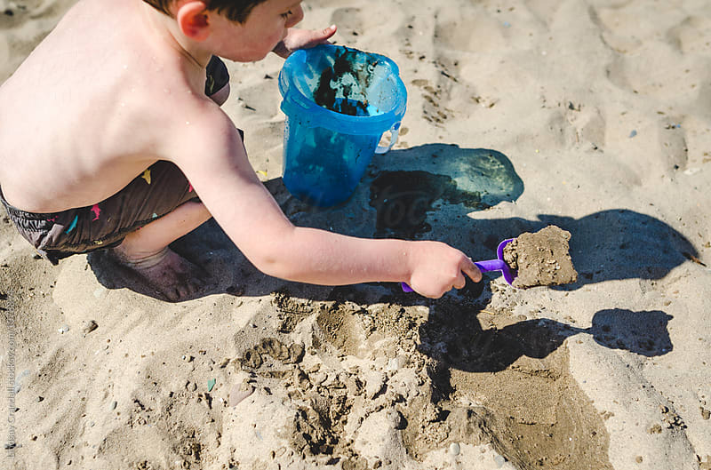 Little boy digging in the sand at the beach by Lindsay Crandall for Stocksy United
