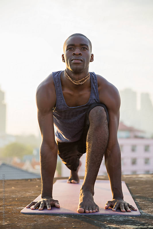 Vertical shot of a dark skinned young man doing yoga on a city rooftop  by Jovo Jovanovic for Stocksy United