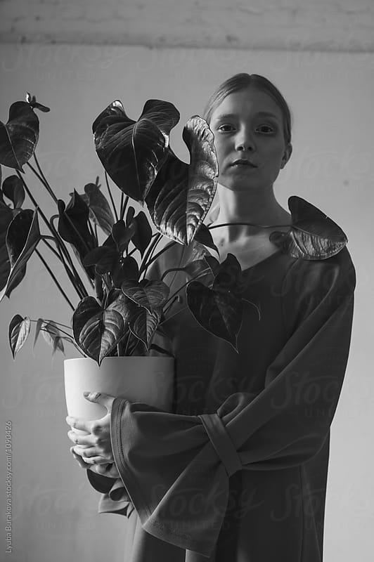 Young woman holding a plant by Lyuba Burakova for Stocksy United