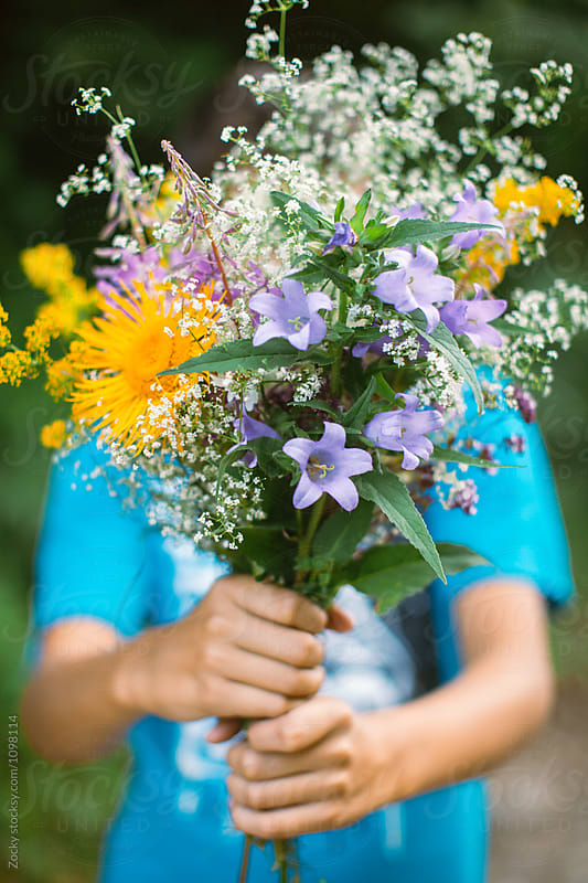Boy holding bunch of wildflowers by Zocky for Stocksy United