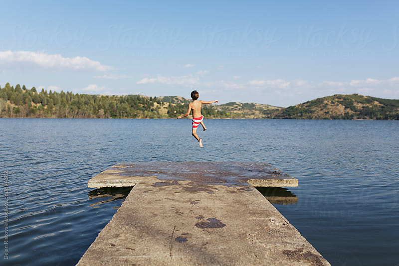 Boy jumping in lake. by Dejan Ristovski for Stocksy United