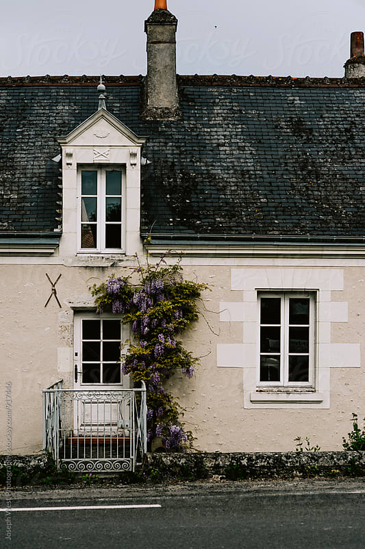 Exterior of a European home with flowers by Joseph West Photography for Stocksy United
