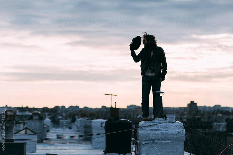 A scruffy man tips his hat on his Brooklyn rooftop  by HOWL for Stocksy United