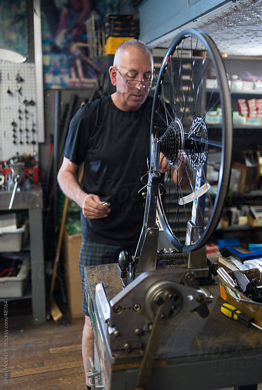 Local Bike Shop: Store Owner at Work in Mechanical Area by Brian McEntire for Stocksy United