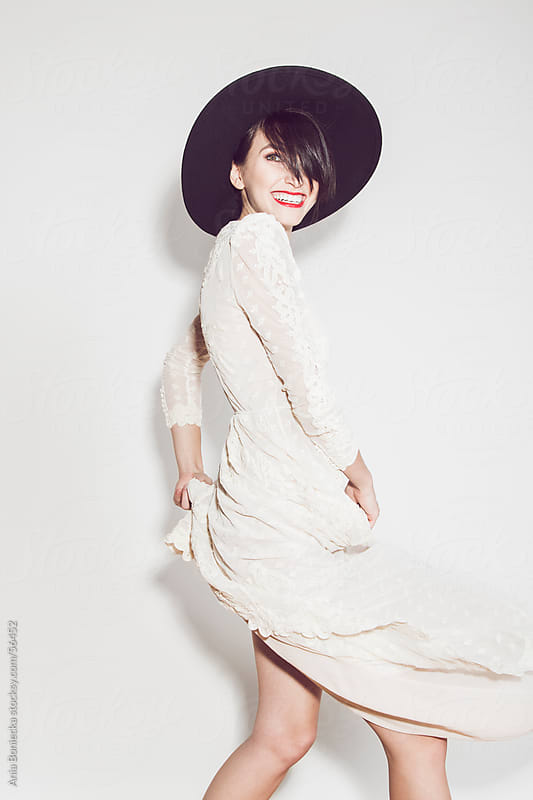 Beautiful woman swaying her white dress, wearing a hat by Ania Boniecka for Stocksy United