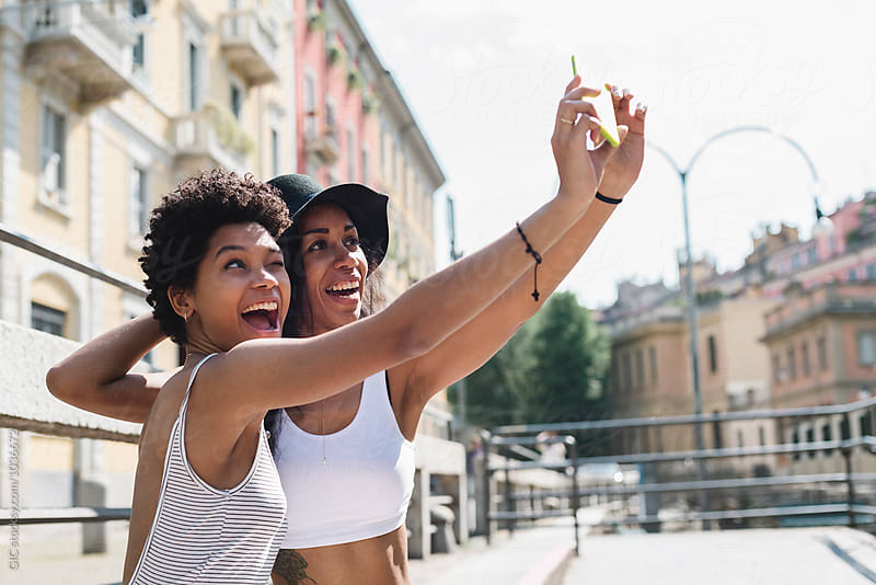 Two friends taking a funny selfie outdoors by Simone Becchetti for Stocksy United