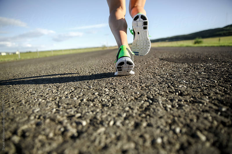 a close up of running shoes running away from camera down a paved road by Shaun Robinson for Stocksy United