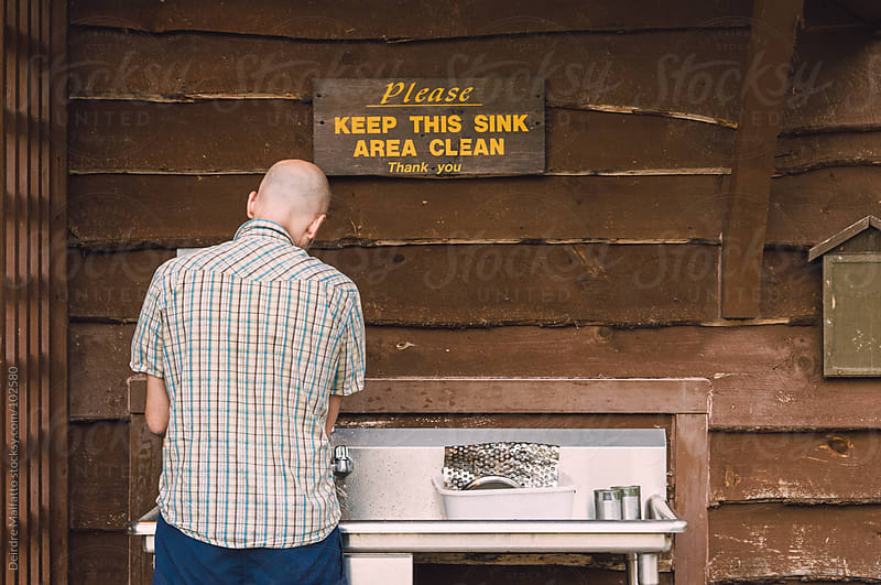 man washing dishes while camping by Deirdre Malfatto for Stocksy United