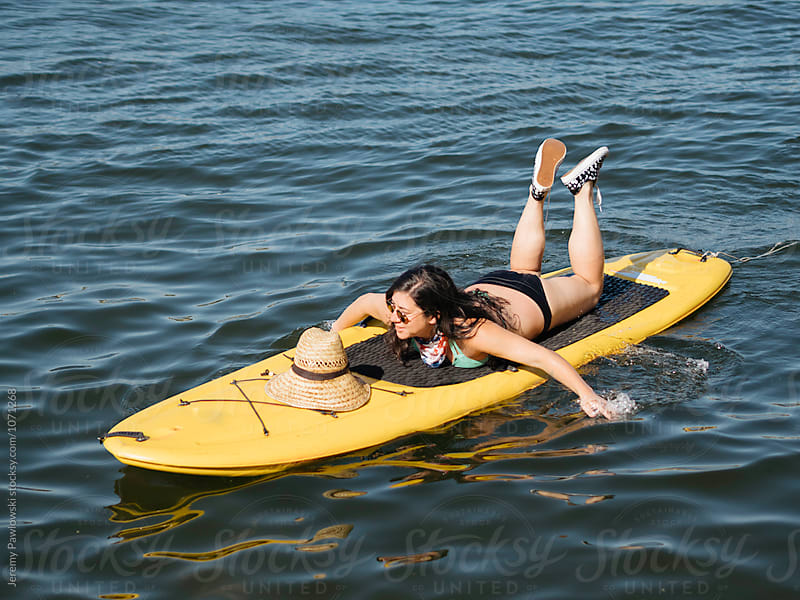Mixed race Asian woman laying down on yellow paddle board in lake water by Jeremy Pawlowski for Stocksy United