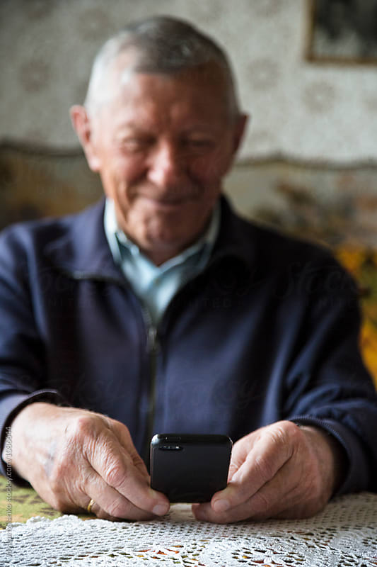 Senior smiling while looking at the cellphone  by Jovana Milanko for Stocksy United