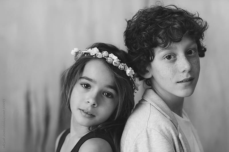 Portrait of a little girl with flower crown and boy by Miquel Llonch for Stocksy United