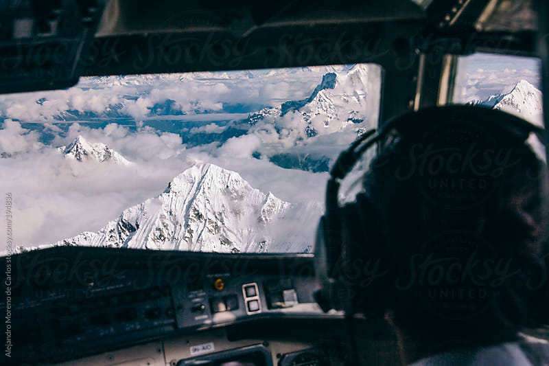 Pilot on airplane cockpit flying over Himalaya mountains by Alejandro Moreno de Carlos for Stocksy United