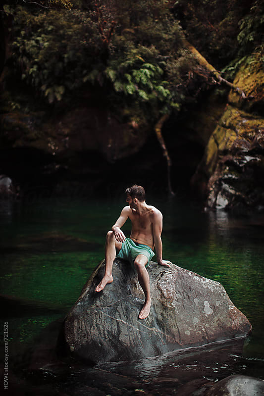 A young man rests on a rock in the middle of a summer swimming hole by HOWL for Stocksy United