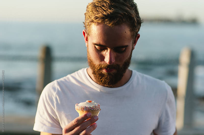 Man and a Cupcake by Bruce and Rebecca Meissner for Stocksy United