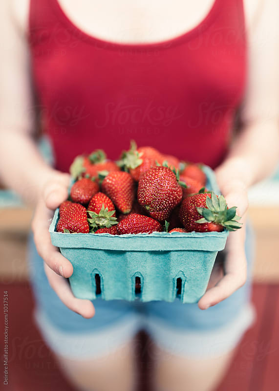 girl in red and blue with red strawberries by Deirdre Malfatto for Stocksy United