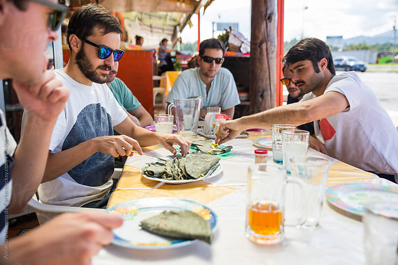 Group of young men having traditional exotic food for lunch in a restaurant outside by Alejandro Moreno de Carlos for Stocksy United