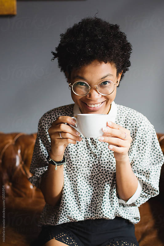 Happy woman drinking a cup of coffee  by michela ravasio for Stocksy United