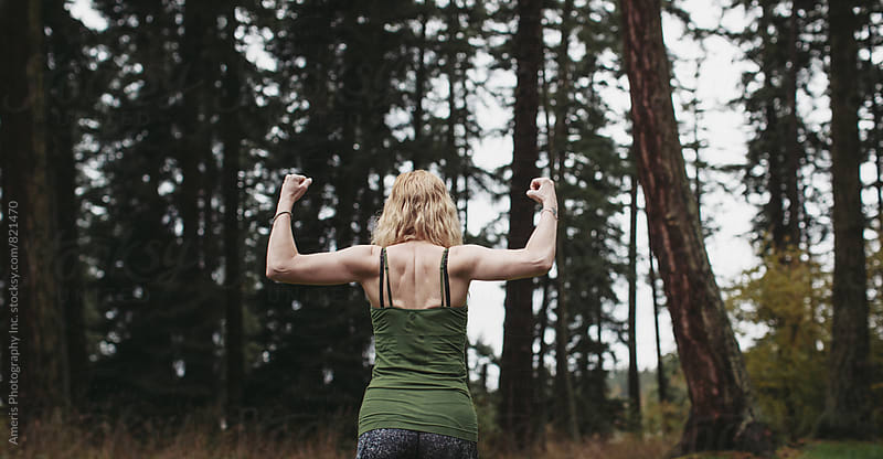 Middle age woman flexing back muscles in forest by Rob and Julia Campbell for Stocksy United