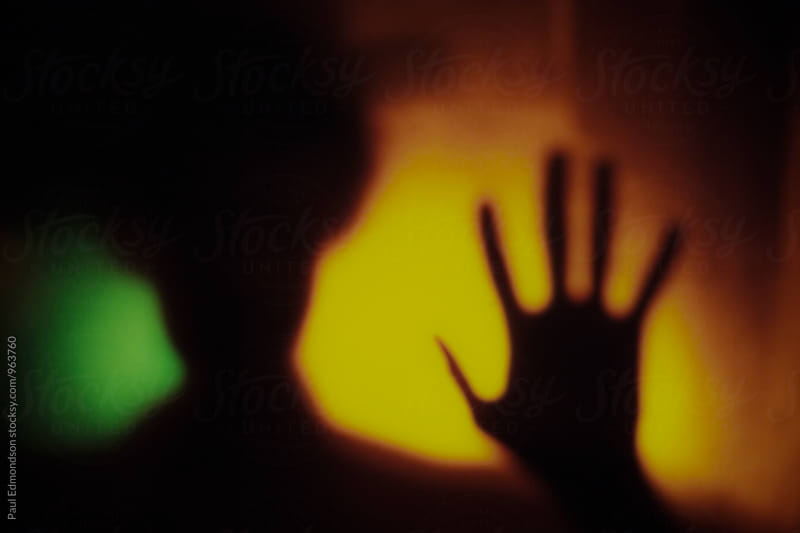 Blurred focus abstract of man with hand raised, glowing lights in background  by Paul Edmondson for Stocksy United
