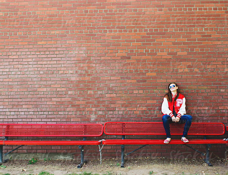 teen girl sits on back of metal bench leaning on brick wall by Tana Teel for Stocksy United