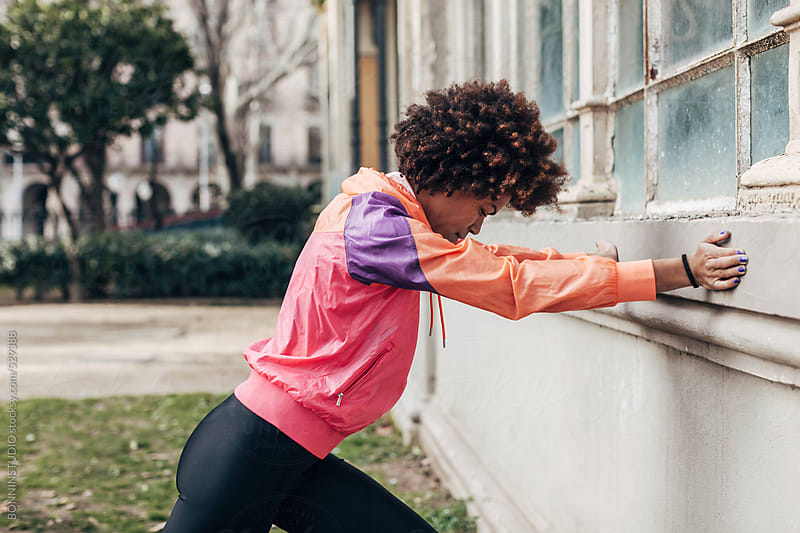 Young african american woman doing stretching exercises in the park. by BONNINSTUDIO for Stocksy United