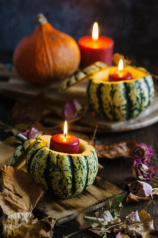 Autumn still life: jack-o-lanterns and candles on table with dried flowers and autumn leafs.  by Darren Muir for Stocksy United