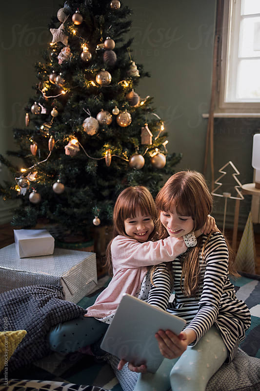 Sisters Take a Selfie on a Tablet at Christmas by Lumina for Stocksy United