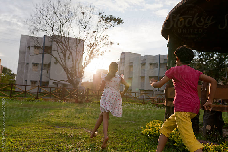Teenage girls running and playing in a park by PARTHA PAL for Stocksy United