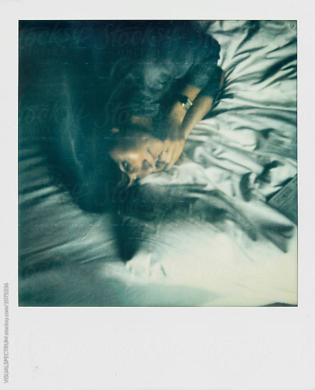 Polaroid Overhead Shot of Young Woman Lying on Bed With Eyes Open by VISUALSPECTRUM for Stocksy United