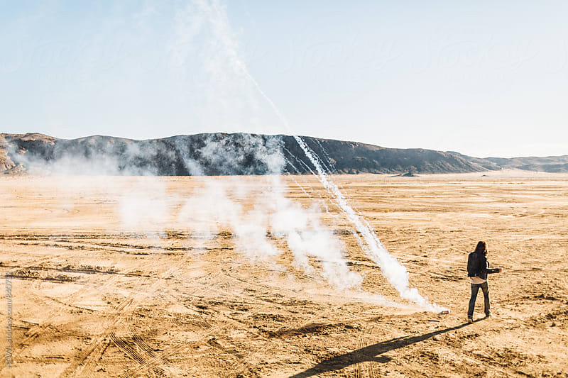 A lone man releases smoke in the desert  by HOWL for Stocksy United