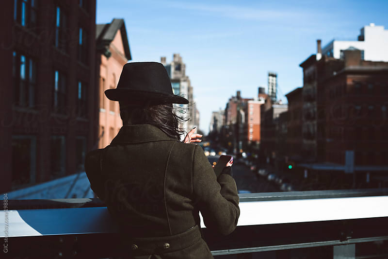 Woman taking a picture with a phone from the highline in New York by GIC for Stocksy United