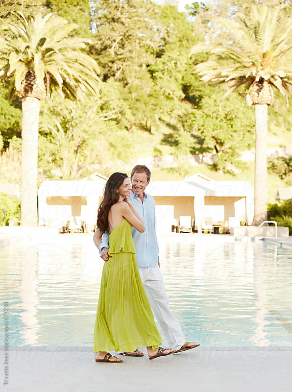 Beautiful couple relaxing and having fun by pool at luxury resort by Trinette Reed for Stocksy United
