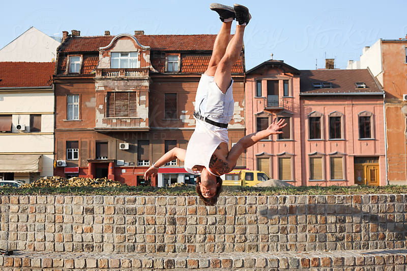 Man jumping in front of a buildings in the city center  by Marija Mandic for Stocksy United