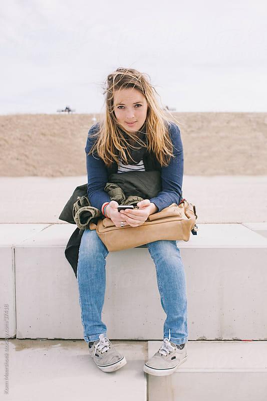 Girl holding her mobile phone while sitting in the sun by Koen Meershoek for Stocksy United