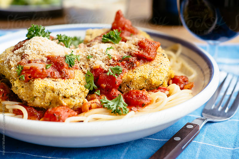 Chicken parmesan on spaghetti by Harald Walker for Stocksy United