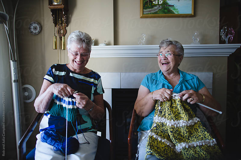 Two senior women knitting together nd laughing by Rob and Julia Campbell for Stocksy United