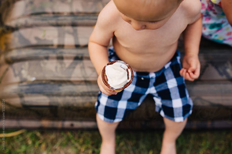 Toddler boy eating ice cream cone by Jessica Byrum for Stocksy United