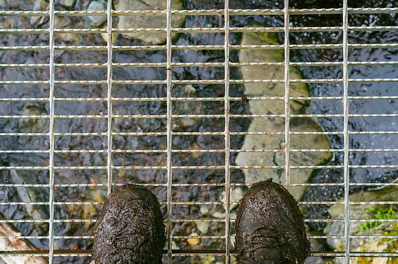 Muddy boots on a suspension bridge by Richard Brown for Stocksy United