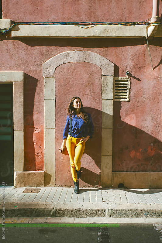Woman standing in front a old red house from la Barceloneta, Barcelona. by BONNINSTUDIO for Stocksy United