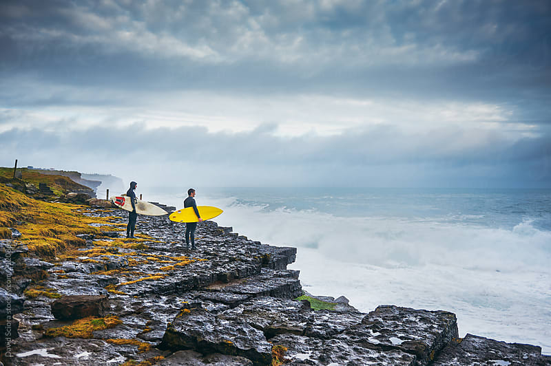 Surfers looking at the stormy ocean from the cliff by David Sciora for Stocksy United